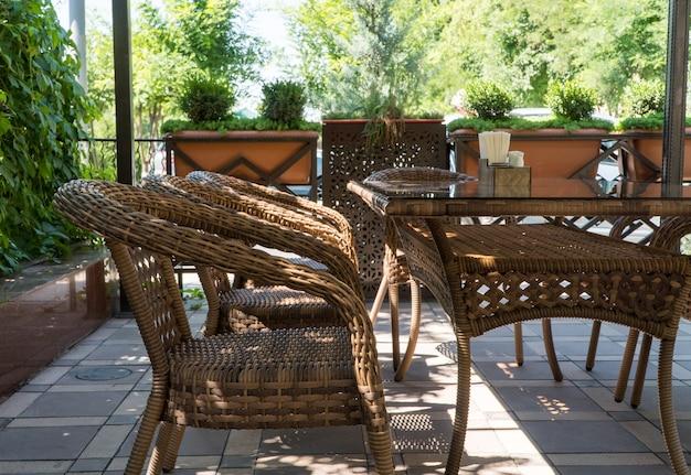 Stoły i wiklinowe krzesła w letniej kawiarni na świeżym powietrzu z klombami
