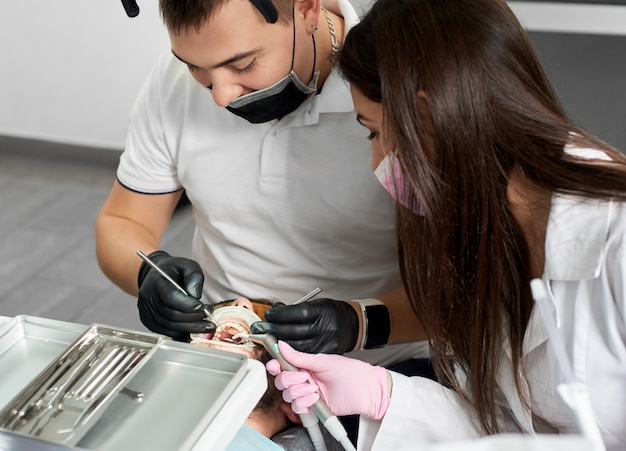 Stomatolog pracuje nad pacjentem płci męskiej za pomocą koferdamu. młoda asystentka pomaga jej w stomatologii w szpitalu dzięki nowym technologiom