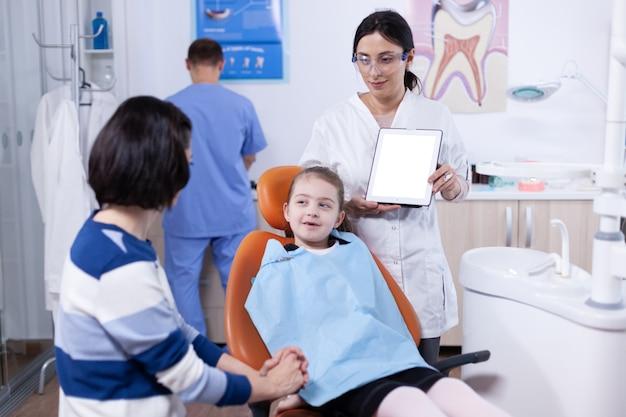 Stomatolog rozmawia o higienie jamy ustnej z młodym rodzicem i dzieckiem. stomatolog wyjaśniający profilaktykę zębów matce i dziecku trzymającemu tablet pc z dostępnym miejscem na kopię.