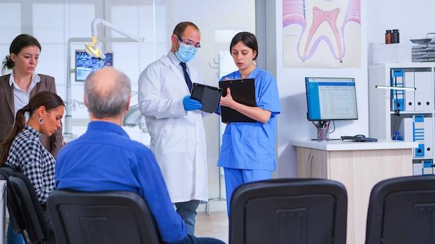 Stomatolog rozmawia z asystentką stojącą w poczekalni kliniki stomatologicznej przed badaniem pacjentów, pielęgniarka robi notatki w schowku, podczas gdy lekarz patrzy na tablet.