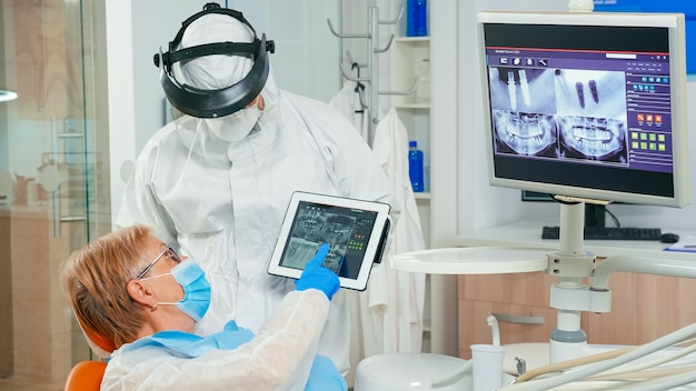 Stomatolog z osłoną twarzy przegląda prześwietlenie zęba ze starszym pacjentem wyjaśniającym leczenie za pomocą tabletu w pandemii covisd-19. zespół medyczny noszący kombinezon ochronny, kombinezon, maskę i rękawiczki.