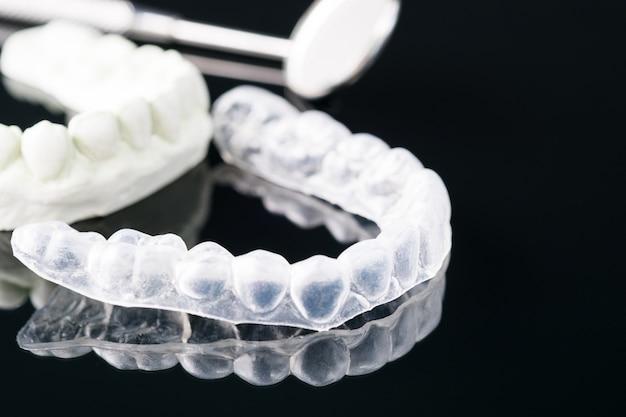 Stomatologiczni narzędzia i ustalający ortodontyczny urządzenie na czarnym tle.