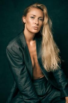 Stonowana seksowna kobieta w męskim garniturze na nagim ciele z długimi blond włosami na ciemnym tle w studio