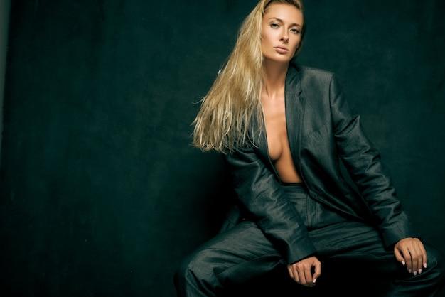 Stonowana seksowna kobieta w męskim garniturze na nagim ciele z długimi włosami na ciemnym tle w studio