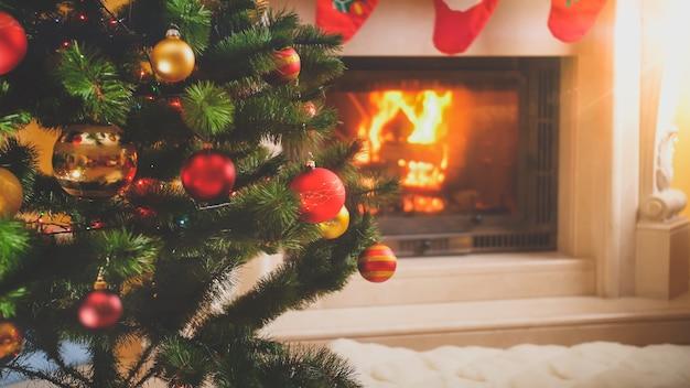 Stonowane świąteczne tło z kominkiem i choinką w salonie