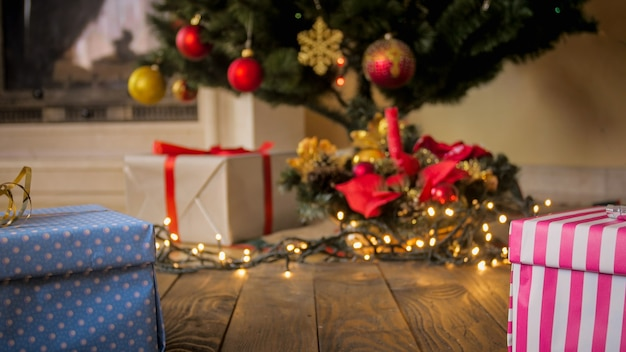 Stonowane tło świecących świateł i stos prezentów pod choinką w salonie