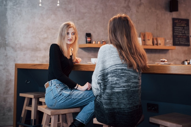 Stonowane zdjęcie najlepszych przyjaciół mających randkę w kawiarni lub restauracji. piękne dziewczyny rozmawiają lub komunikują się podczas picia kawy