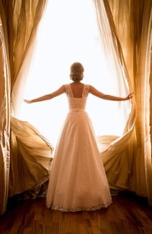 Stonowane zdjęcie pięknej panny młodej pozującej w oknie w pokoju hotelowym?