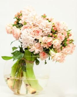 Stonowane zdjęcie pięknych świeżych różowych kwiatów w szklanym wazonie