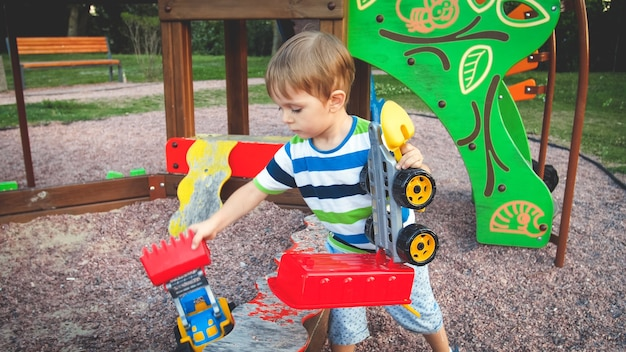 Stonowane zdjęcie słodkiego małego chłopca bawiącego się zabawkową ciężarówką i przyczepą na placu zabaw w parku