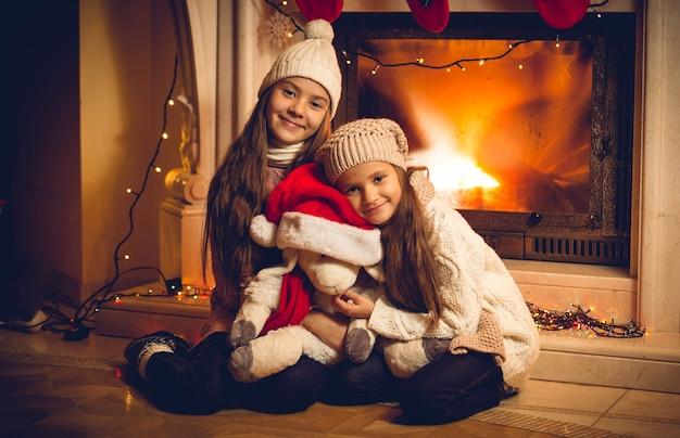 Stonowane zdjęcie w starym stylu przedstawiające dwie szczęśliwe dziewczyny siedzące z zabawką przy kominku w wigilię bożego narodzenia