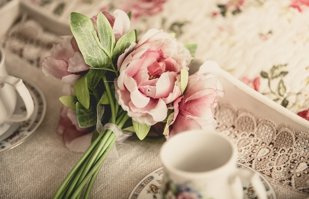 Stonowane zdjęcie w stylu retro przedstawiające różowe kwiaty leżące na tacy z filiżankami herbaty