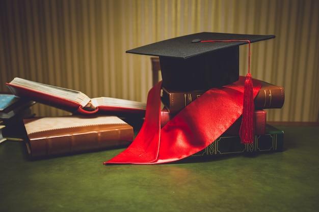 Stonowane zdjęcie z bliska czerwonej wstążki i czapki ukończenia szkoły na klasycznym stole