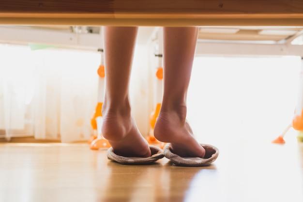 Stonowane zdjęcie zbliżenie dziewczyny zakładającej kapcie po przebudzeniu