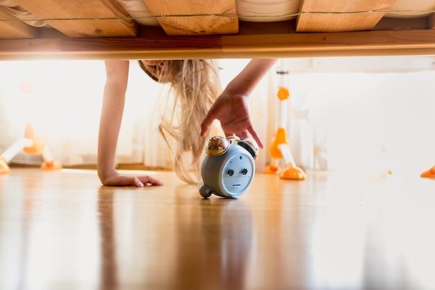 Stonowane zdjęcie zirytowanej dziewczyny sięgającej po budzik pod łóżkiem wczesnym rankiem