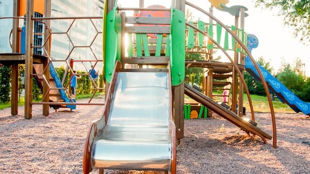 Stonowany obraz dużego drewnianego placu zabaw z mnóstwem drabin i zjeżdżalni w parku