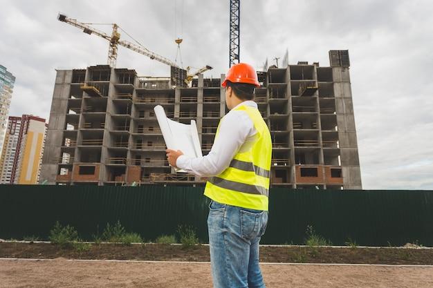 Stonowany obraz inżyniera w kasku i kamizelce kontrolującego plac budowy