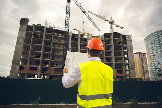 Stonowany obraz młodego inżyniera budowlanego czytającego plany na placu budowy
