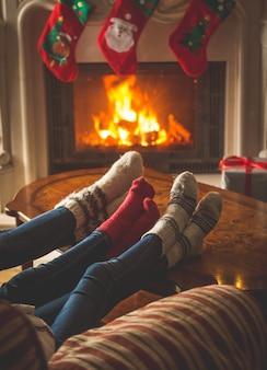 Stonowany obraz pary w wełnianych skarpetkach odpoczywającej przy płonącym kominku