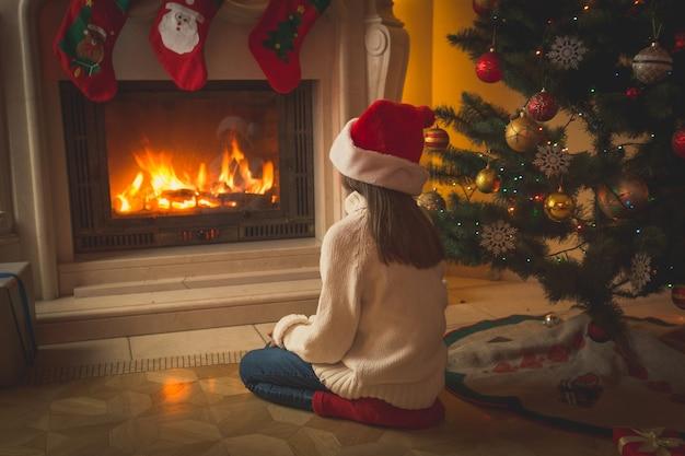 Stonowany obraz pięknej dziewczyny w santa hat siedzącej na podłodze i patrzącej na kominek