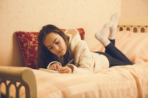 Stonowany obraz pięknej nastolatki leżącej na łóżku z prywatnym pamiętnikiem