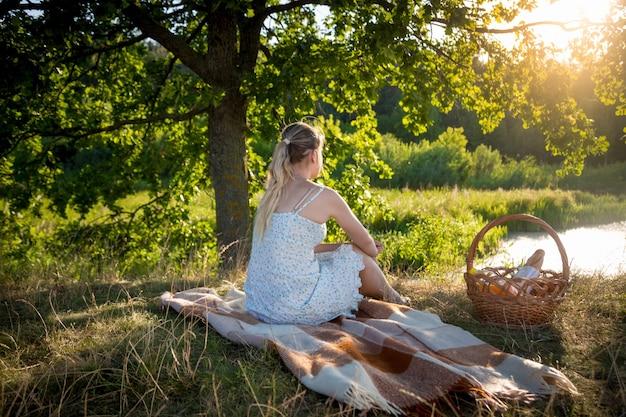 Stonowany obraz pięknej samotnej kobiety relaksującej się pod wielkim drzewem i patrzącej na zachód słońca
