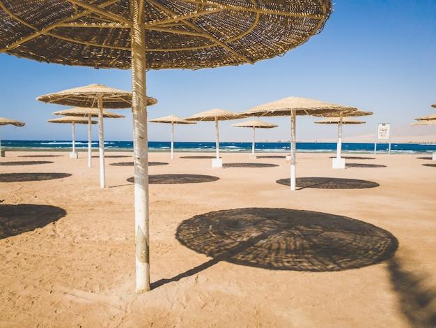 Stonowany obraz pustej plaży morskiej z dużą ilością słomianych parasoli dla ochrony przed słońcem. kryzys w turystyce i podróżach