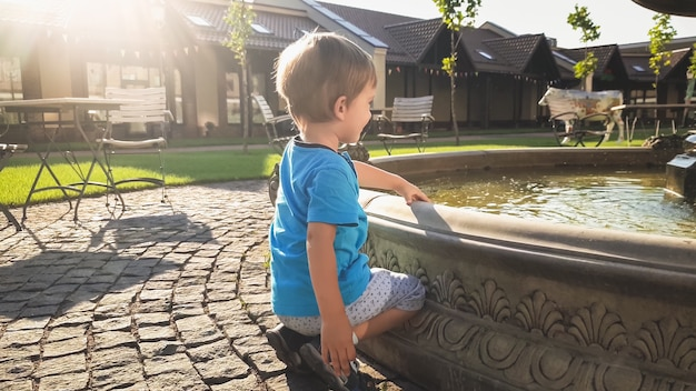 Stonowany obraz uroczego małego chłopca siedzącego obok fontanny na pięknym starym placu w parku