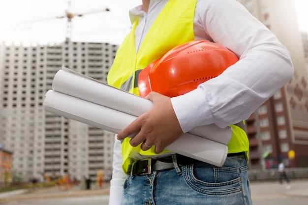 Stonowany obraz zbliżenie młodego architekta pozowanie na placu budowy