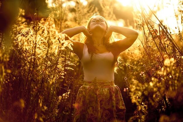 Stonowany portret pięknej młodej kobiety chodzącej po złotym polu w promieniach słońca