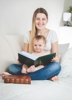 Stonowany portret szczęśliwej młodej matki i jej chłopca pozujących z dużą książką