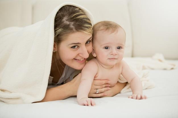 Stonowany portret szczęśliwej młodej matki leżącej z synkiem pod kocem