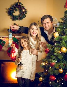 Stonowany portret szczęśliwej rodziny pozuje z lampionami na choince