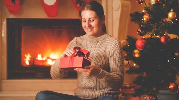 Stonowany portret szczęśliwej uśmiechniętej kobiety siedzącej przy płonącym kominku i choince oraz pakującej prezenty i prezent dla rodziny