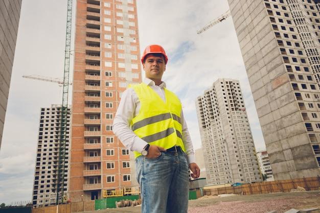 Stonowany portret uśmiechniętego inżyniera pozującego przeciwko budynkom w budowie