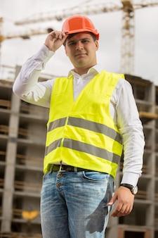 Stonowany portret zbliżenie uśmiechniętego inżyniera budowlanego w kasku hard
