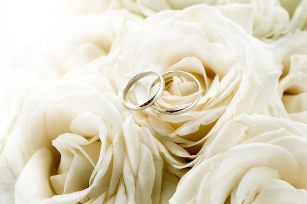 Stonowany widok makro dwóch obrączek ślubnych leżących na bukiecie ślubnym