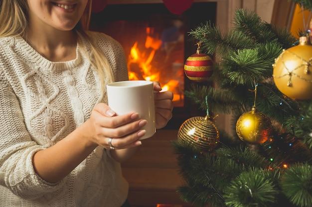 Stonowany wizerunek kobiety w wełnianym swetrze rozgrzewającym się przy kominku przy filiżance herbaty