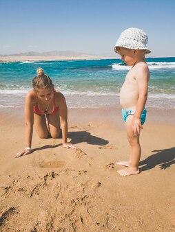 Stonowanych obraz młodej matki grając z jej małym chłopcem na mokrym piasku na plaży. rodzinny relaks i dobry czas podczas letnich wakacji.