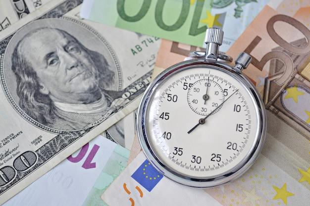 Stoper leżał na banknotach euro i dolarach amerykańskich; skup się na zegarku