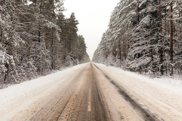 Stopiony śnieg na drodze utwardzonej przez samochód