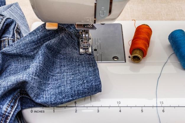 Stopka do maszyny do szycia na dżinsie. nożyczki, szpule nici. stoi na stole