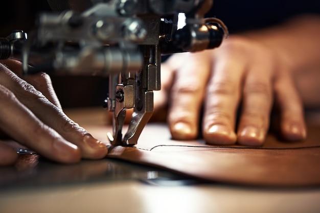 Stopka do maszyny do szycia rękami mistrza zbliżenia, krawiec robi szew na kawałku skóry na maszynie do szycia, koncepcja szycia wyrobów skórzanych.