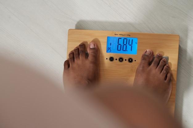 Stopy bosej kobiety stojącej na wadze