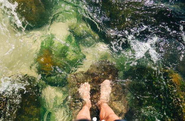Stopy człowieka stojącego w wodzie morskiej na kamieniu koralowym, widok z góry. koncepcja wakacji letnich