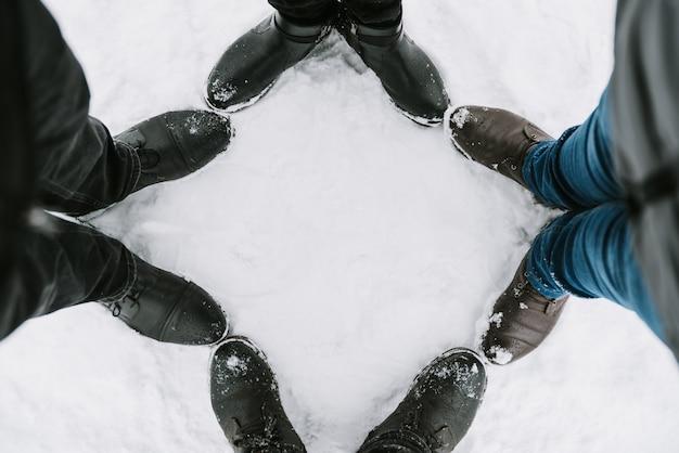 Stopy czterech osób w śniegu z bliska