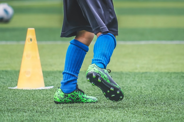 Stopy dziecka ćwiczą bieganie i poruszanie się na boisku piłkarskim