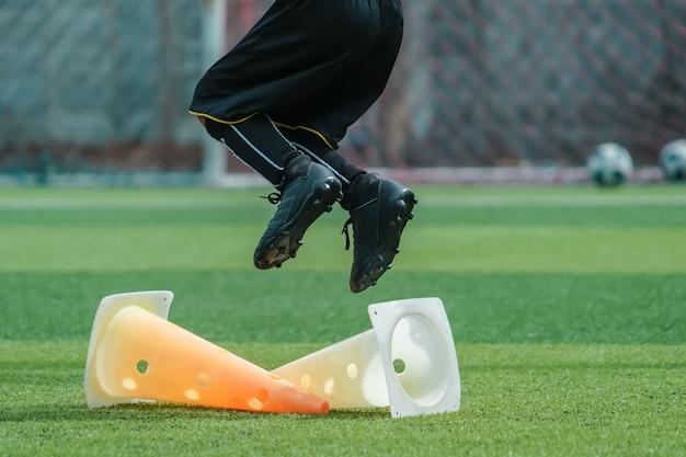 Stopy dziecka ćwiczą skakanie po stożku na boisku piłkarskim