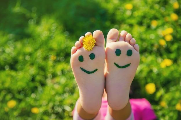 Stopy dziecka na trawie rysowanie uśmiechu
