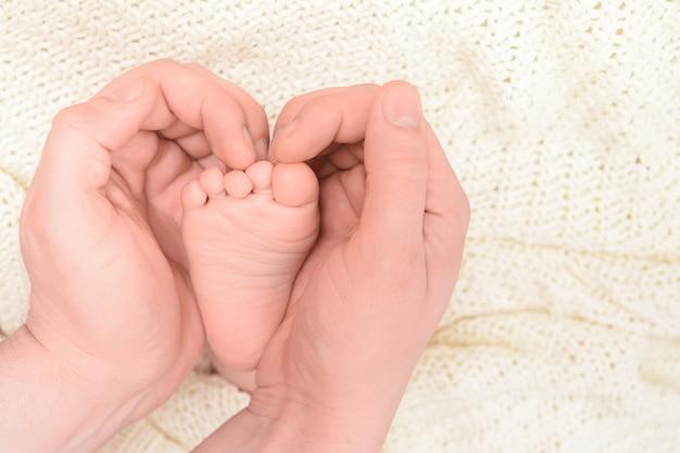Stopy dziecka w męskich rękach w kształcie serca z miękkim tłem